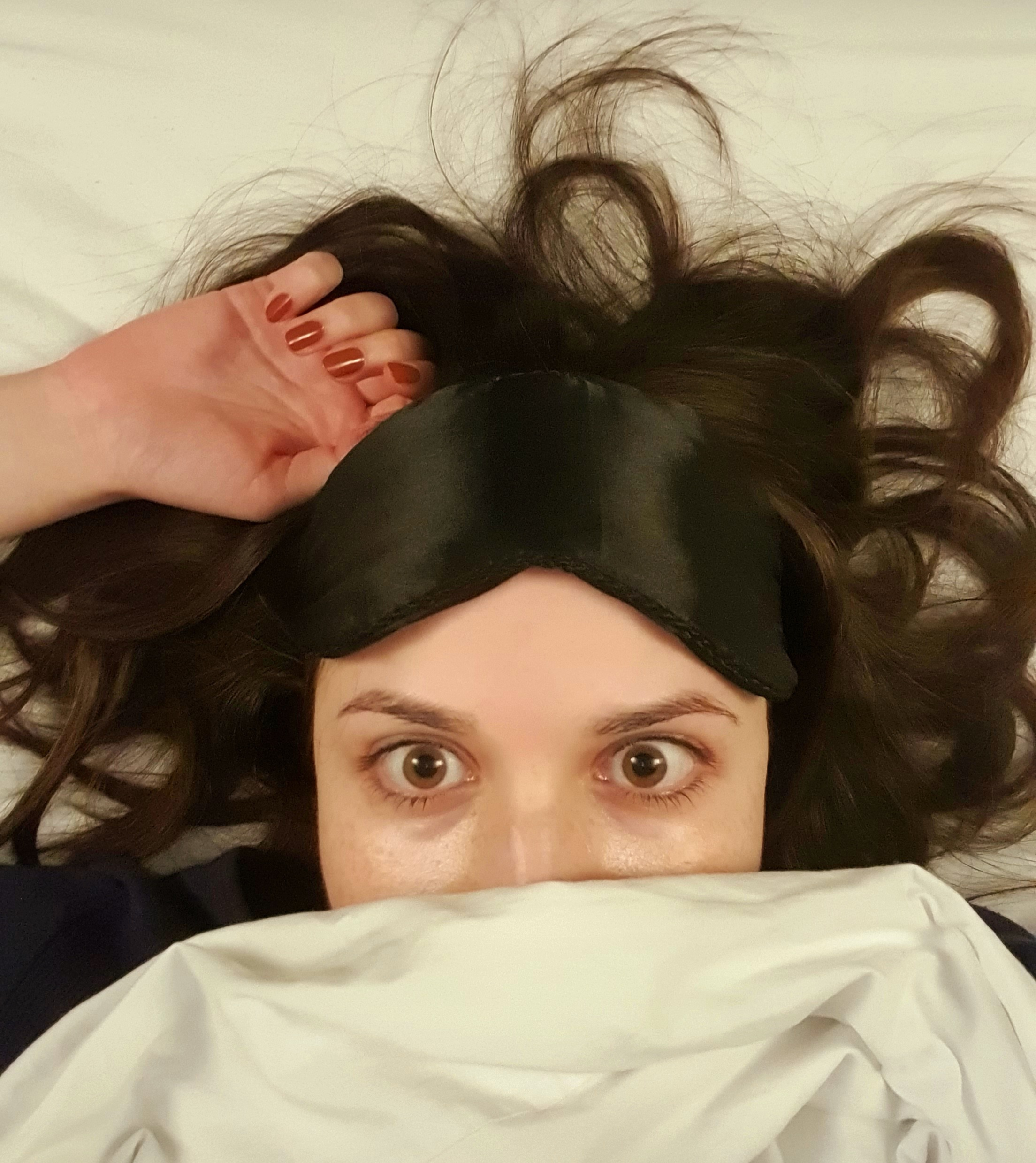 A close-up of the author, Jess, lying in bed, looking exhausted. Her hair is tousled and she is wearing an eye-mask just above her wide eyed stare.