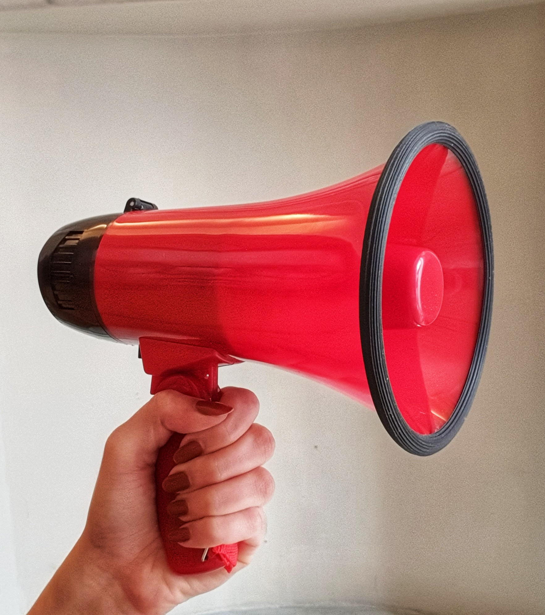 A close-up of the author, Jess' hand grasping a large, red megaphone.