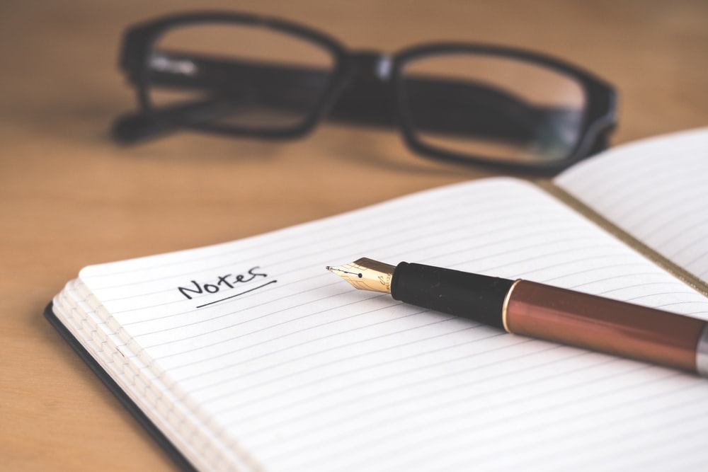 """A lined notebook with the word """"notes"""" written at the top and an old fashioned pen on top of it. A pair of glasses are out of focus in the background."""