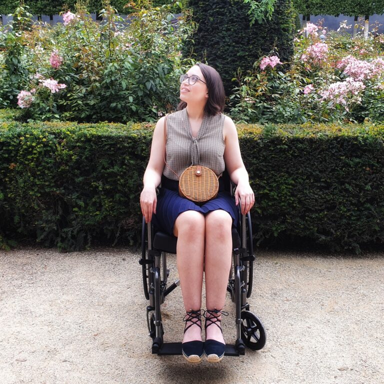 The author, Jess, sits in a wheelchair gazing up towards an unseen object. The photo is in a garden with a soft, dreamy focus.