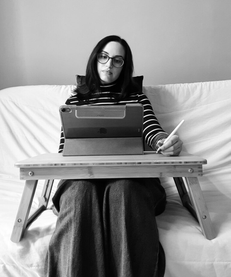 The author, Jess, sitting on her couch with a lapdesk and writing on her ipad.