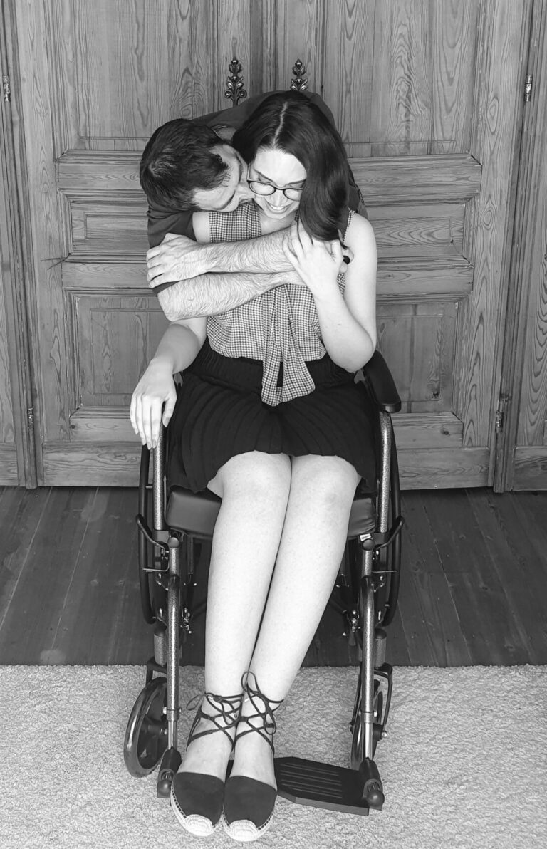 Jess sitting in a wheelchair, getting a hug from her fiance, Haydn.