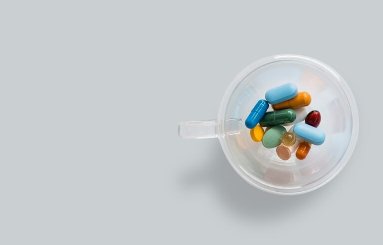 A cup of brightly coloured pills.